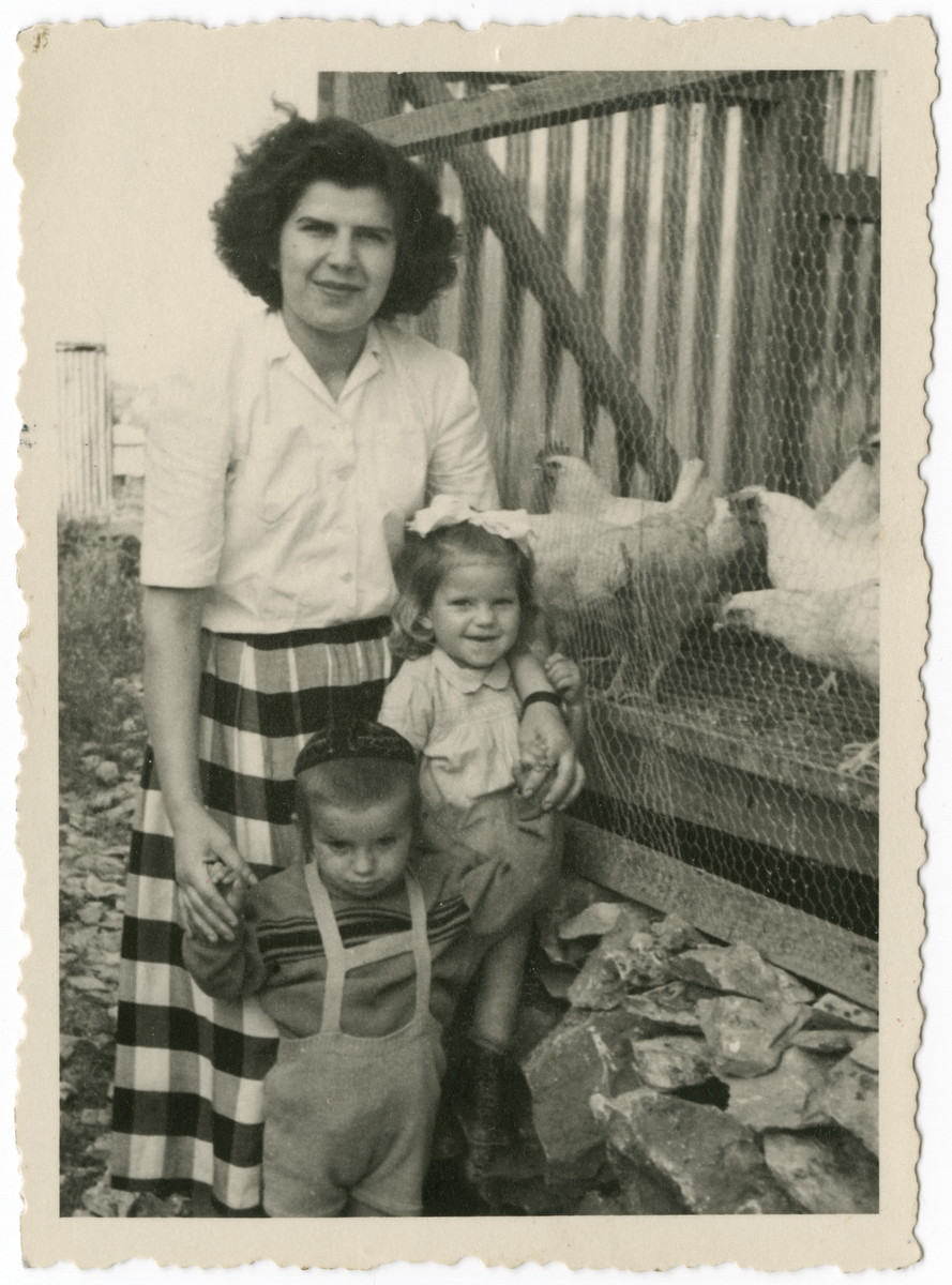 Ruth Salamon (nee Weinberger) poses next to a chicken coop with the children of her sister Helena, Moshie and Rochel.