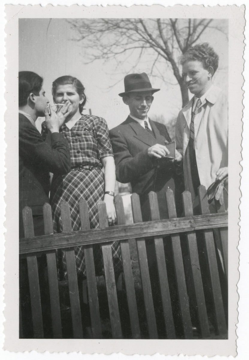 Four young people, two of them sharing a cigarette, stand behind a fence.  Jolan Weinberger is second from the left.  Her cousin Bernard is to her right.