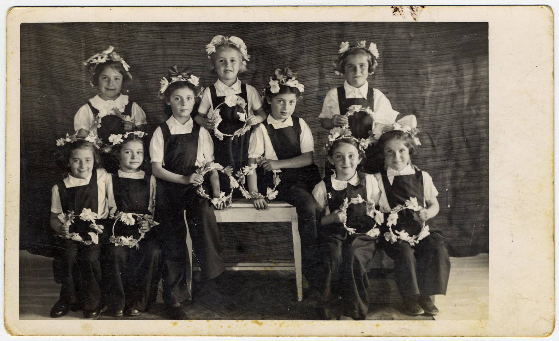 Young girls, dressed in overalls and with flowers in their hair, put on a school performance at the Novaky labor camp.  Among those pictured are Mira Menzer (sitting second from right) and twin sisters (sitting on the table).