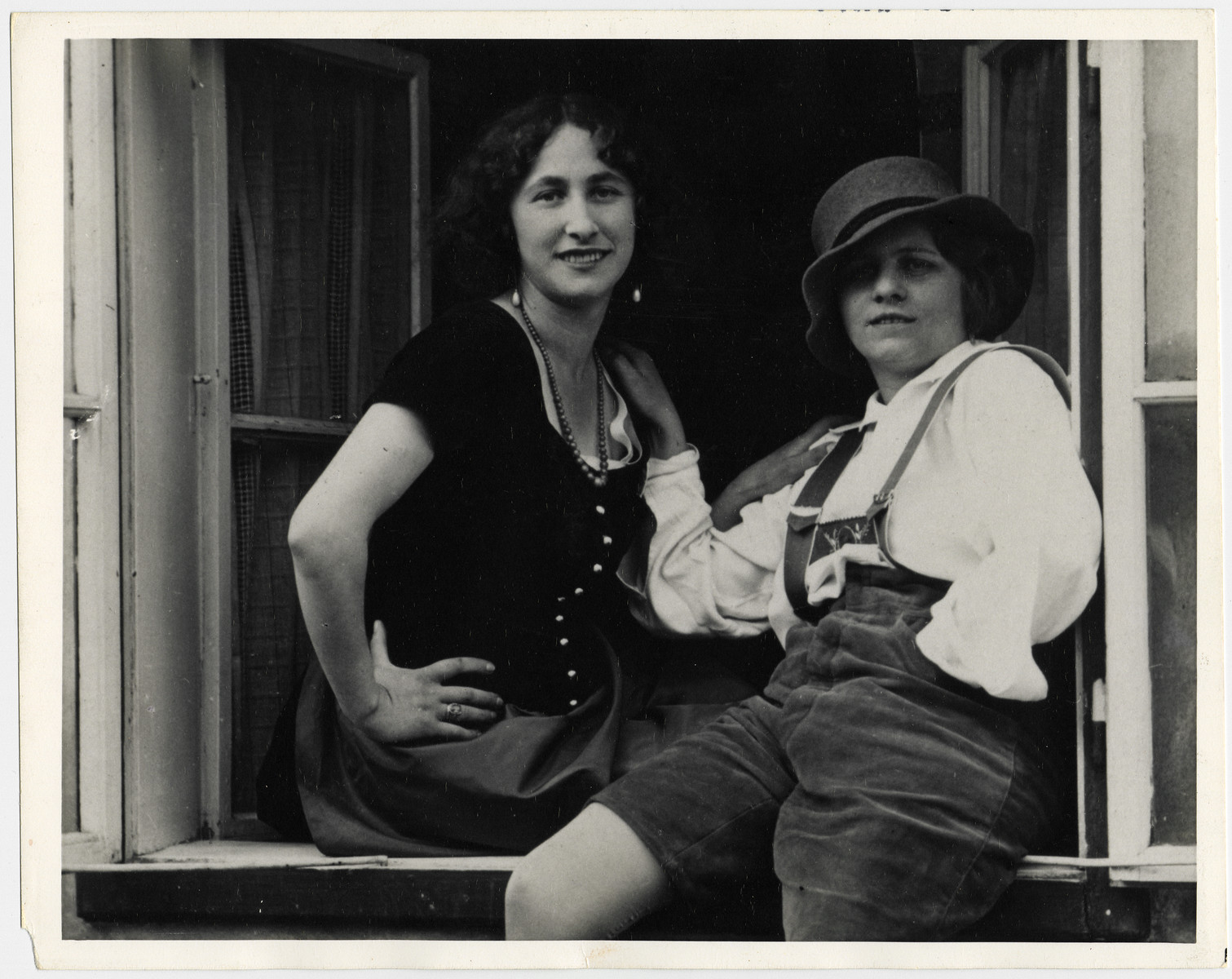 Two Austrian Jewish young women pose on a window ledge.  Martha Deustscher [later Holzmann] is pictured on the left.