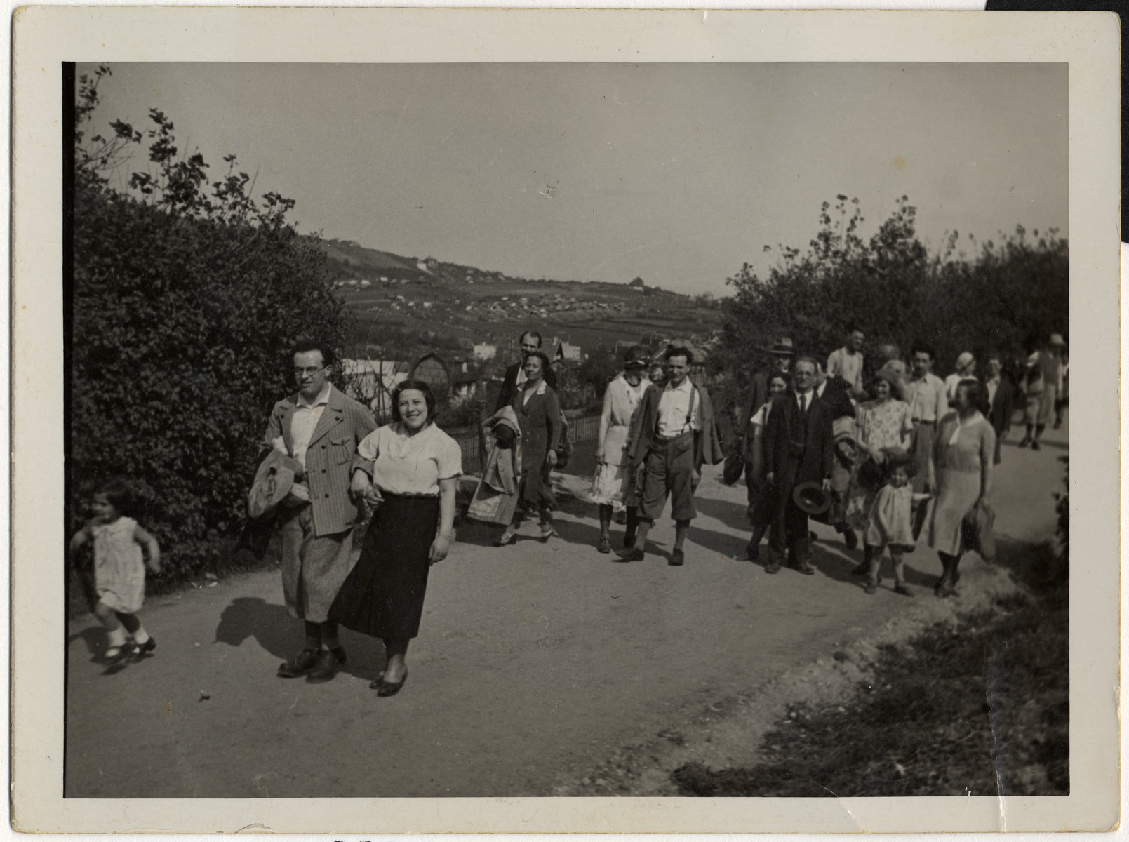 A group of friends on an outing in the country.    Among those pictured are Leo Weiss (front, on left), Mrs. Antler (center back, carrying coat over her arm), Richard Wiener (center, wearing white shirt), Hilda Wiener (far right), and her daughter Nelly (holding her hand).