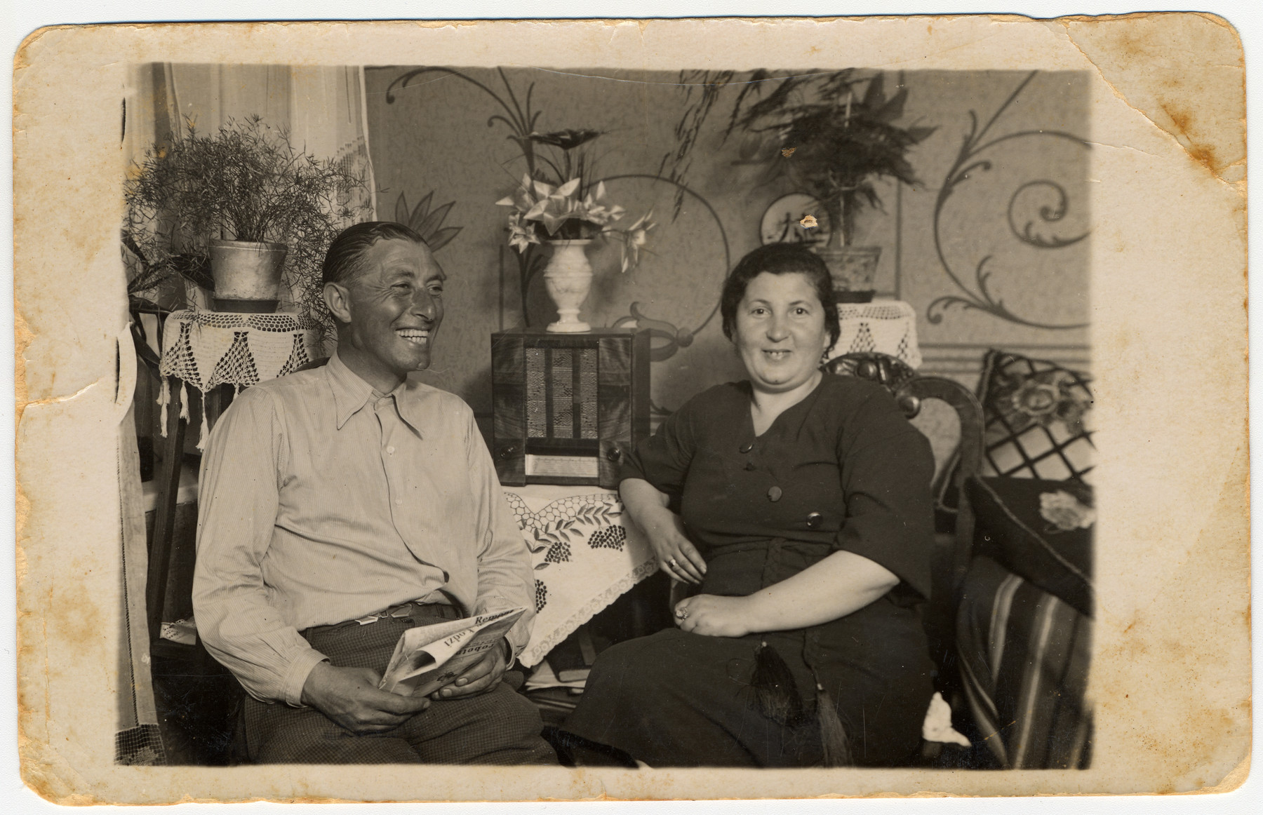 A Jewish couple sits around a small table covered with an embroidered tablecloth in their home.  Pictured are Binyamin and Frymet Bergman, the donor's parents.  Both perished in Auschwitz in 1944.