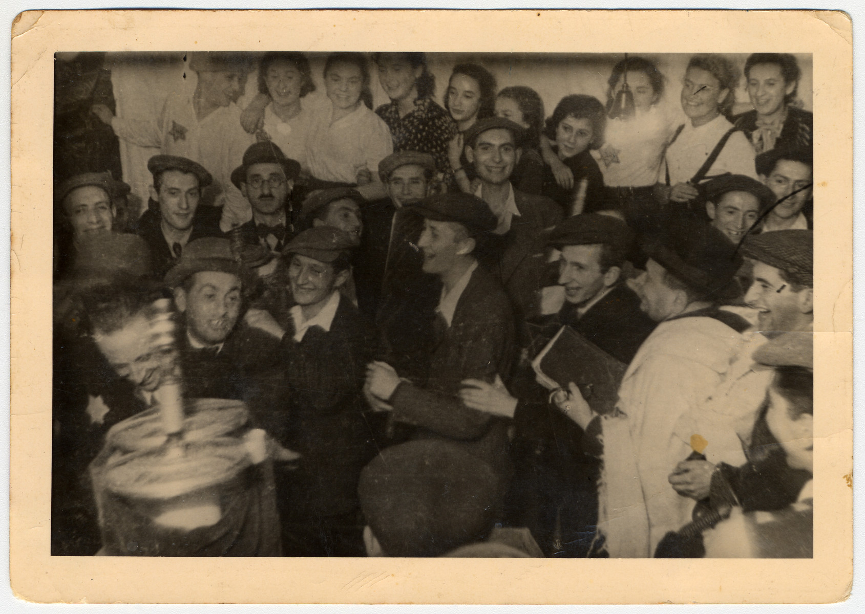 Members of Hanoar Hatzioni, a Zionist youth movement, dance with Torah scrolls in celebration of the Jewish holiday, Simchat Torah,  in the Lodz ghetto.  This was the ghetto's final Simchat Torah celebration.  Pictured from left to right are: Chaim Nata Widawski (perished), Baruch Praszker, Mosze Balzam (age 23, perished), Henryk Bergman (age 20, survived), Josef Lewin (age 23, perished), Najman (age 40) and Marek Margulis (age 21, survived). Second row from left to right are: unknown, Wiktor Sztajn (age 23, survived), Majlech Sziper (age 40), unknown, unknown, and Matatiahu Kohen (age 20, survived). Rozka Grosman (age 21, survived), Mendel Grosman's sister, is pictured second from right in the top row.  Also pictured in the rear are Bronka Zaks (age 21, survived), Menek-Menachem Grossman (age 23), Zosia-Shoshana Grosman (age 20), Shmuel Ginat (age 18, survived).