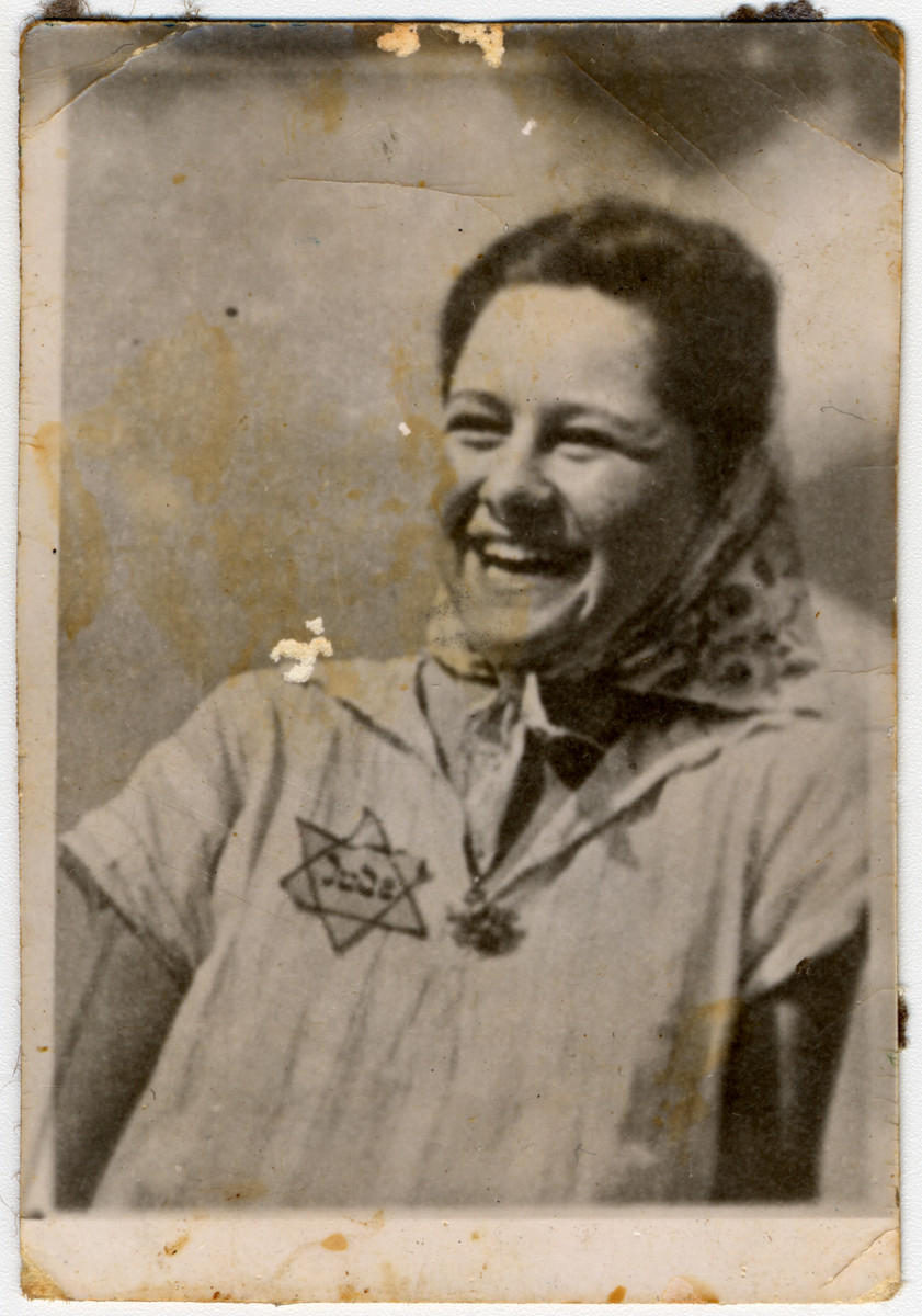 Close-up portrait of a Jewish woman with a badge and a broad smile in the Lodz ghetto.  Pictured is Henia Gorset, a member of Hanoar Hatzioni.