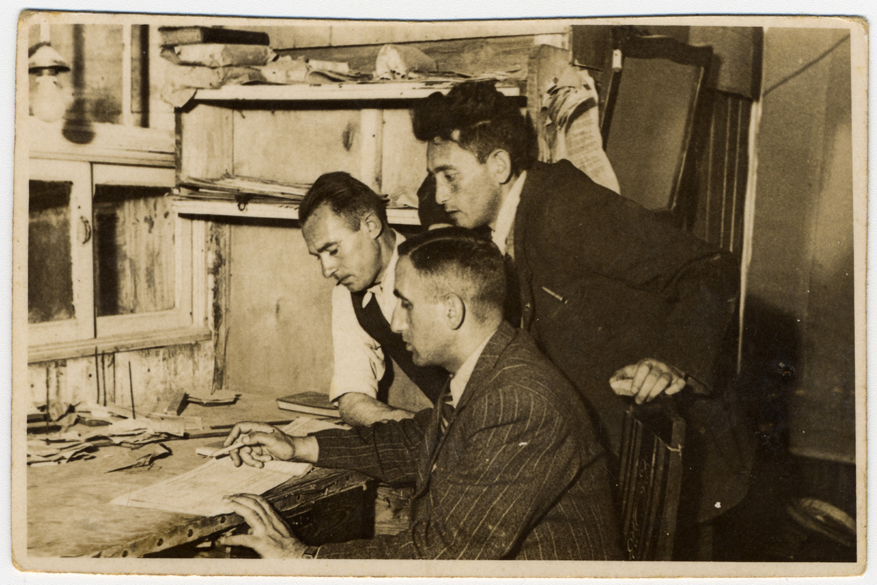 Three men gather around a desk in the statistical department of the Lodz ghetto.  Pictured are Ratner and Rubinek (originally from Prague, Czechoslovakia).