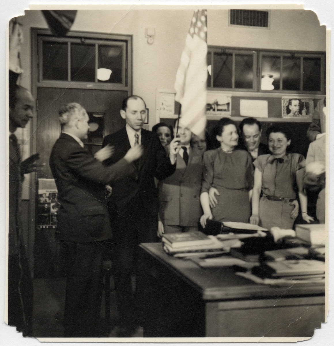 Students in an English language class pledge allegiance to the flag.  Among those pictured are Hilda Wiener Rattner (back row, to the left of the flag), Richard Wiener (behind flag), Meta Novak, a German Holocaust survivor (front, center), and William and Charlotte Friedman, from Hungary (right).