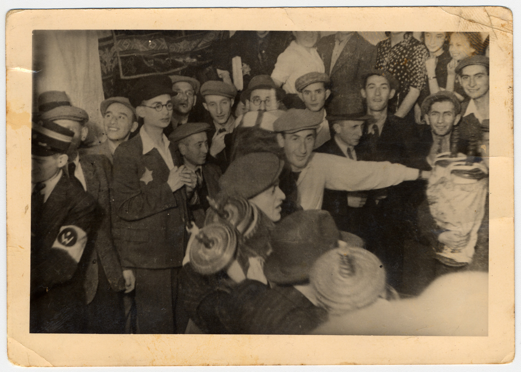 Members of Hanoar Hatzioni, a Zionist youth movement, dance with Torah scrolls in celebration of the Jewish holiday, Simchat Torah,  in the Lodz ghetto.  Standing far left with glasses is Josef Urizon and next to him, facing the camera, is Aron Jakubson.  Behind him, partially hidden is Melech Sziper.  First from right is Matatiahu Cohen, third from right is Wiktor Sztajn and next to him, from profile, is Chaim Nata Widawski.