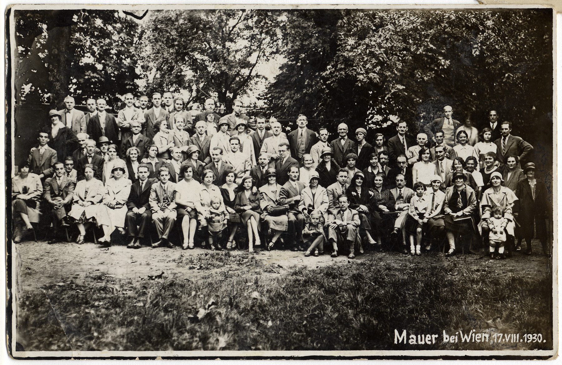 Group portrait of a club gathering.  Among those pictured are Hilda Wiener (seated in front, eighth from the left), her daughter Nelly (standing in front of her), Richard Wiener (second/third row, behind Hilda and wearing light colored shirt), and Leo Weiss (?) (standing second to the right of Richard).