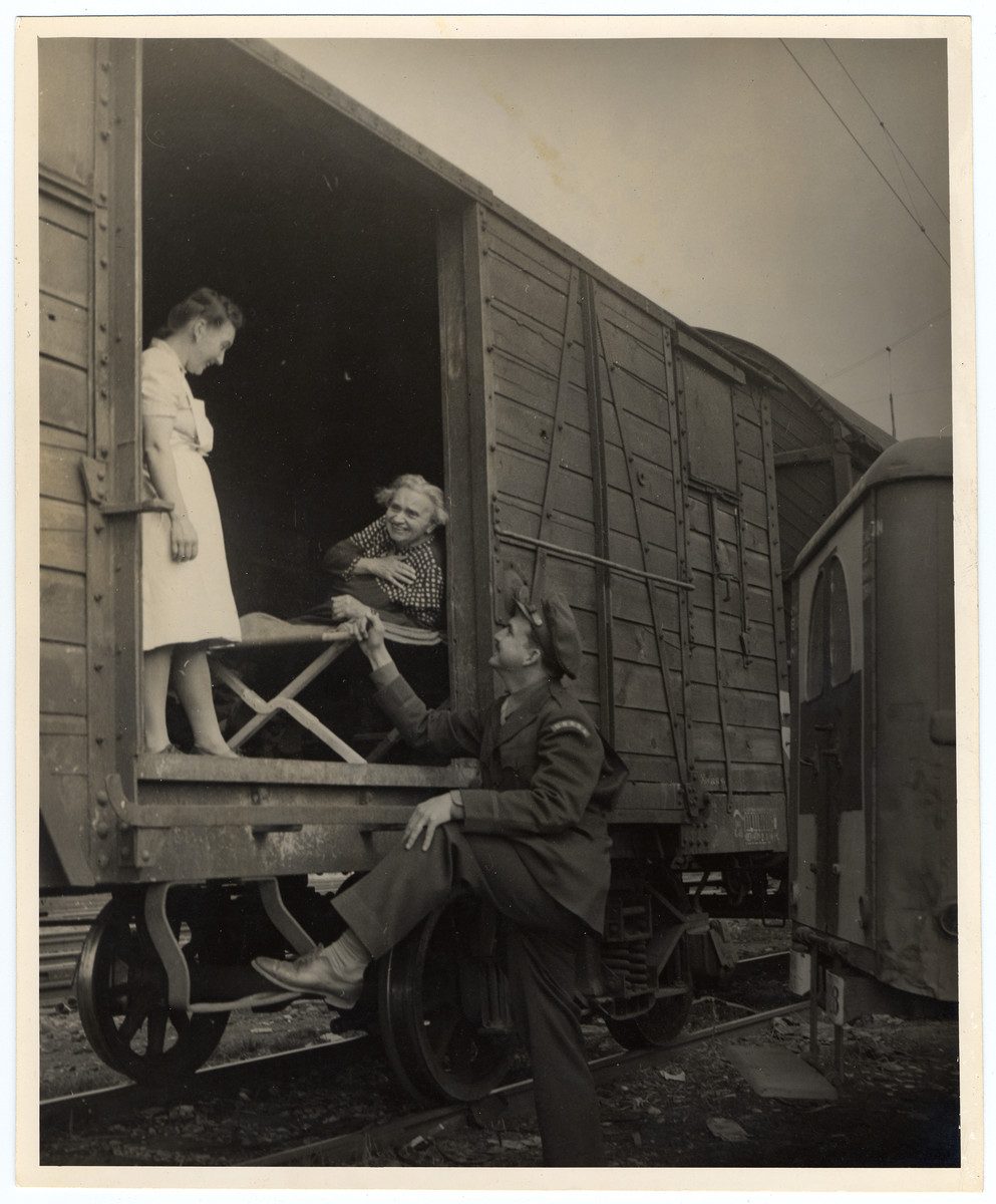 An UNRRA workers says farewell to an infirmed woman leaving Germany on a U.S. Army train.