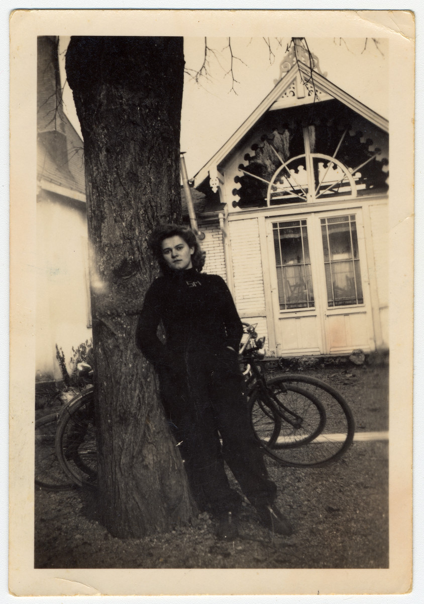 A young woman leans against a tree.   Pictured is Betty Jacubowicz, who helped to smuggle 52 children to Switzerland.  After one year spent in Switzerland, she went to Belgium decided to help smuggle children to Switzerland.  She was arrested on the Swiss border together with her parents and sent to Auschwitz where the parents perished.  Betty survived.