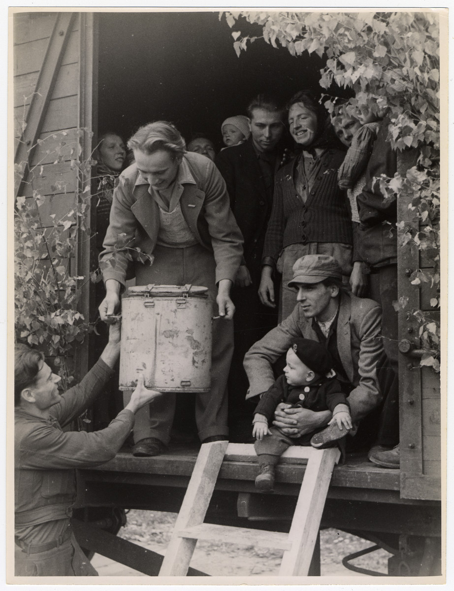 A man lifts a large pot [probably of food] up to another man standing at the entrance to a train about to depart Germany.