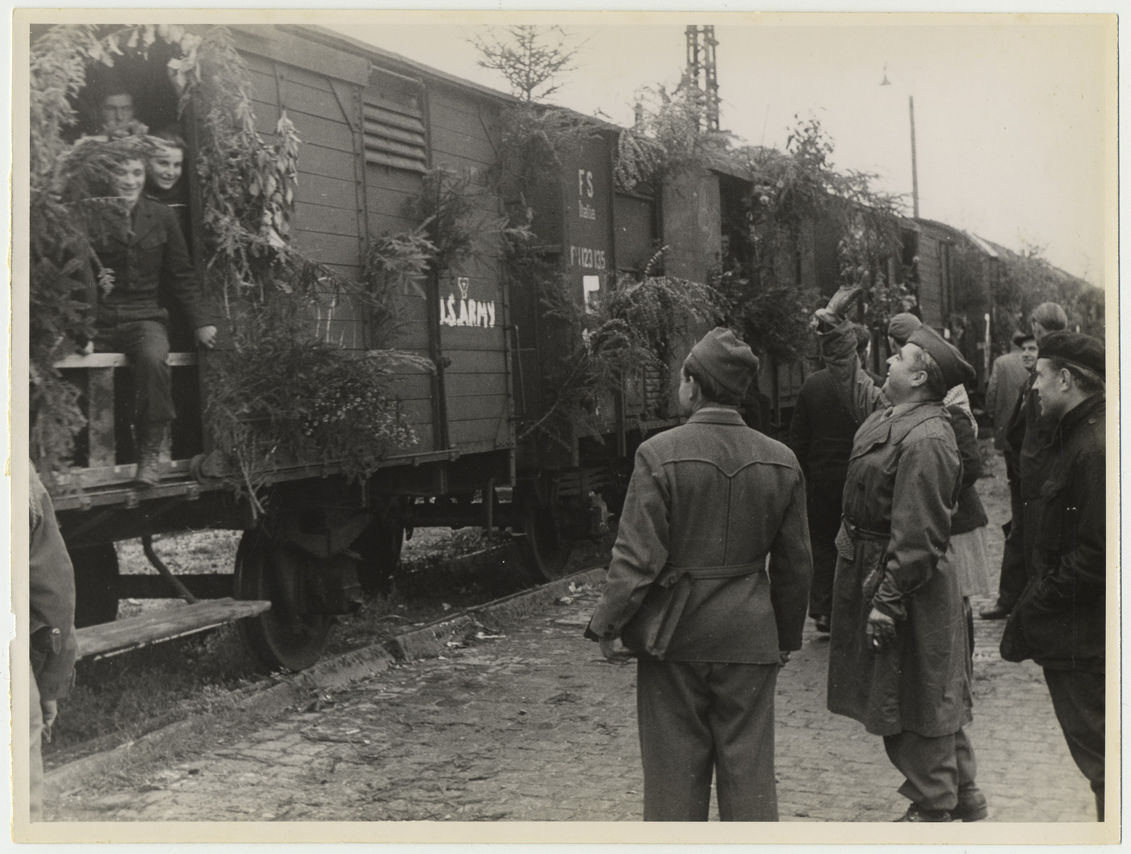 UNRRA workers say farewell to displaced persons leaving Germany on a decorated U.S. Army train.