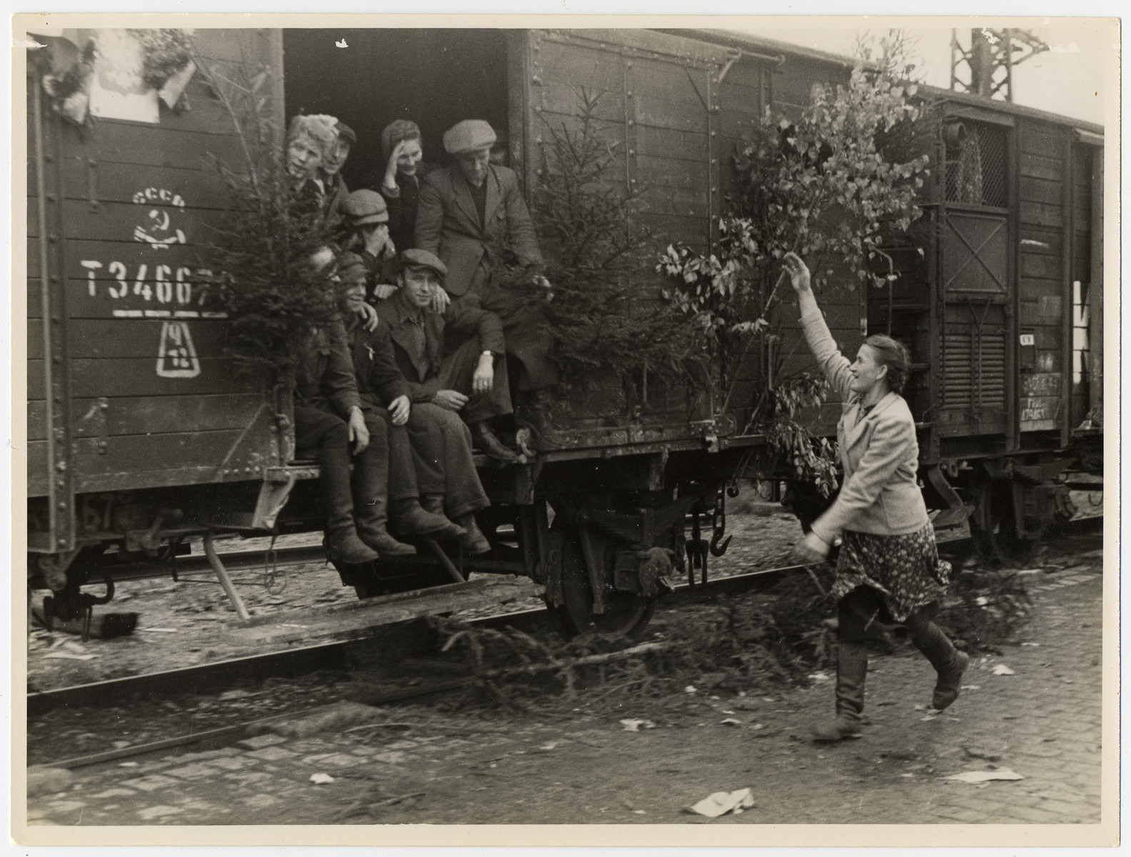 A woman waves farewell to displaced persons leaving Germany on a decorated U.S. Army train.