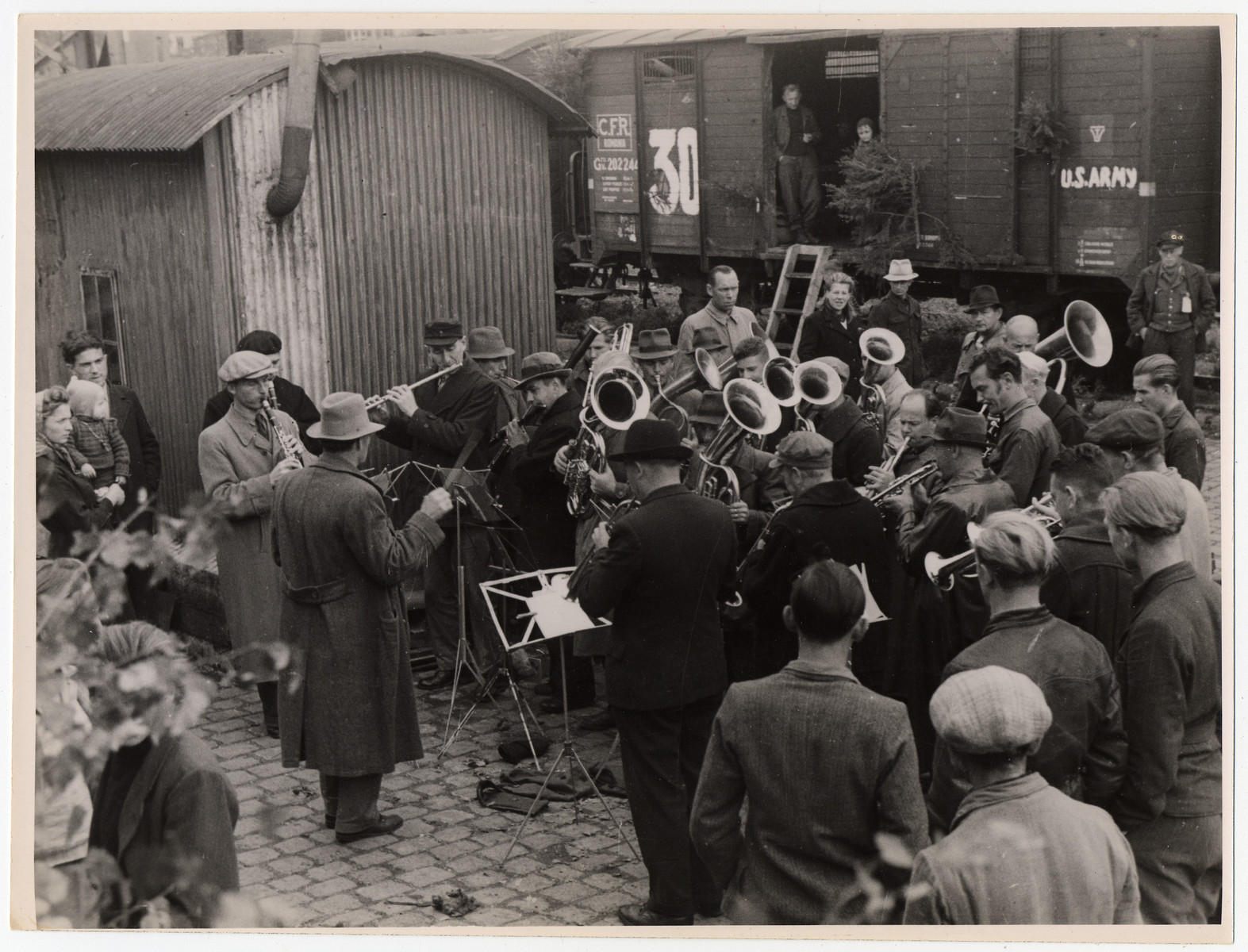 An orchestra performs at a train station as a send-off to a group of displaced persons leaving on a U.S. army train.