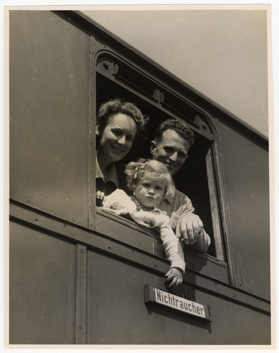 A couple and their young child look out the window of a U.S. Army train that is about to transport them from Germany.