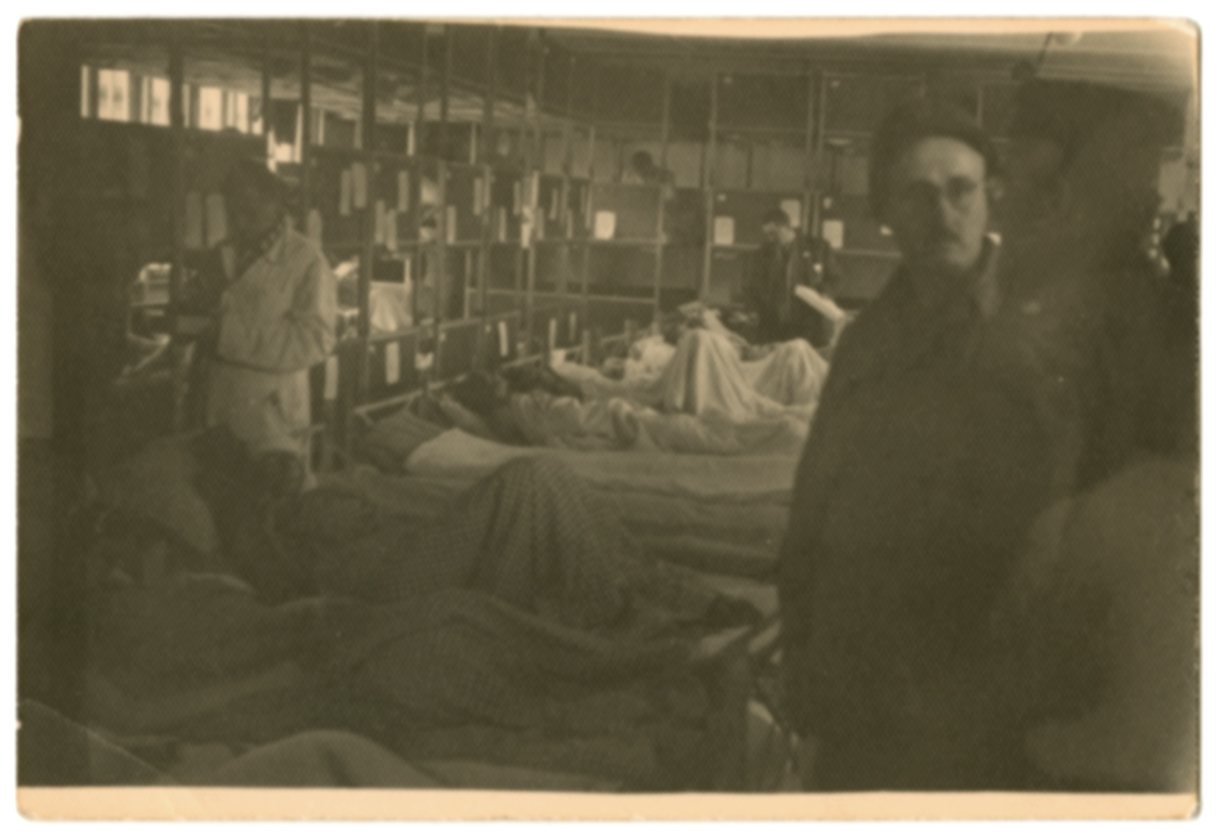 Survivors rest on cots in a makeshift hospital shortly after the liberation of Dachau.
