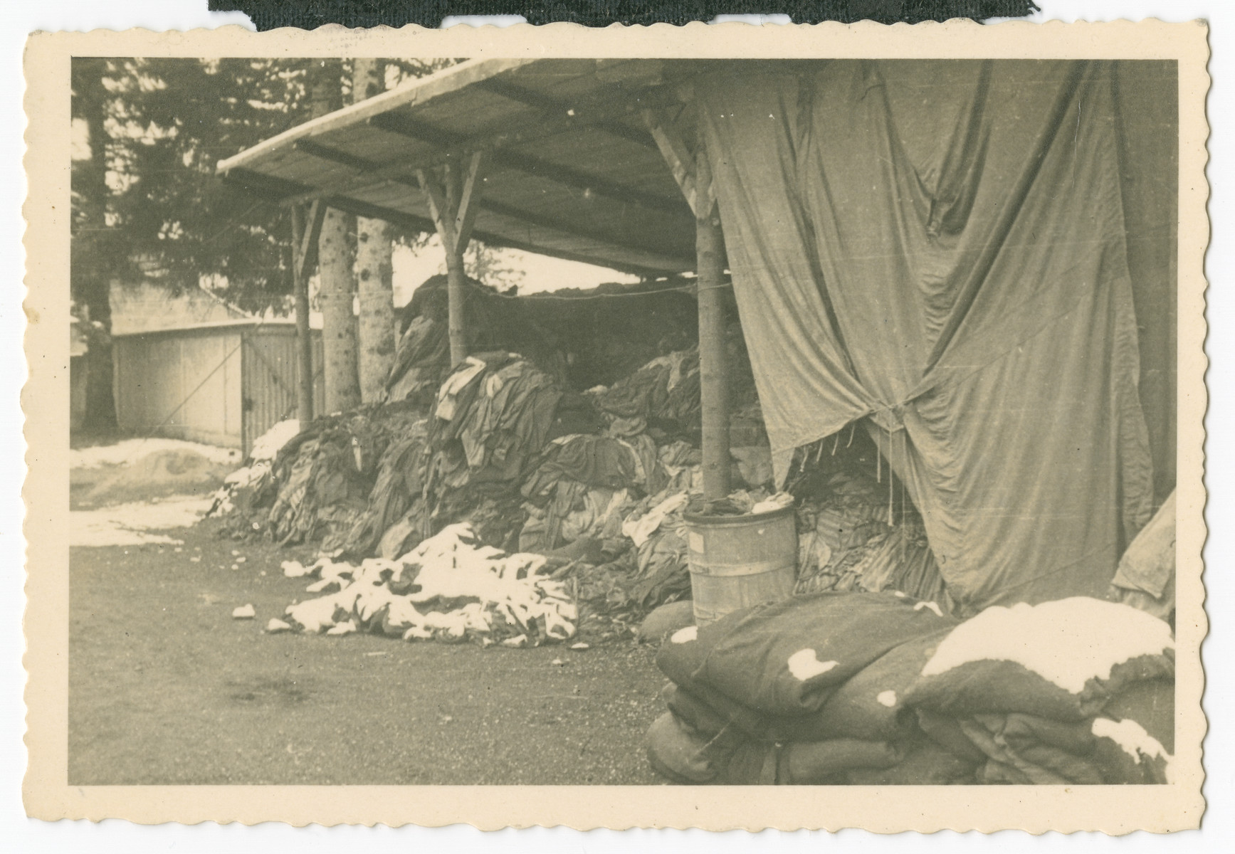 "A photograph taken of clothing pile near the crematoria  Caption on back: ""This one is near the entrance to the furnace where bodies were striped [stripped] of clothing before being burned."""