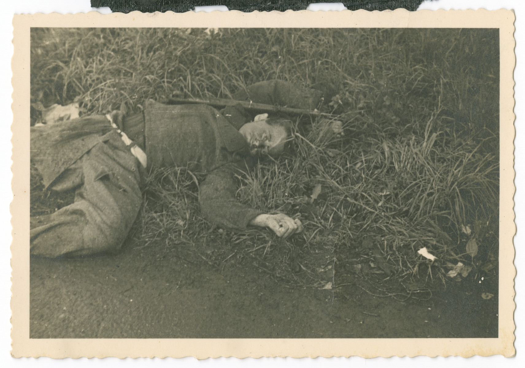 "An SS man killed in an act of revenge lies on the ground of Dachau..  Caption on back: ""When we drove near to the camp the prisoners that were able began to revolt against the guards. This man is one of the casualties inflicted by [sic] the SS guards."