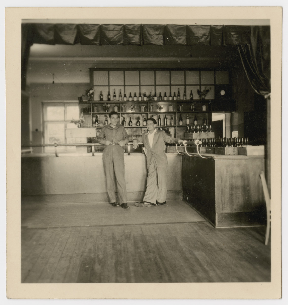 "Two men pose by the bar in the Bergen-Belsen displaced persons camp.  The original caption reads: ""Sam's Canteen."""