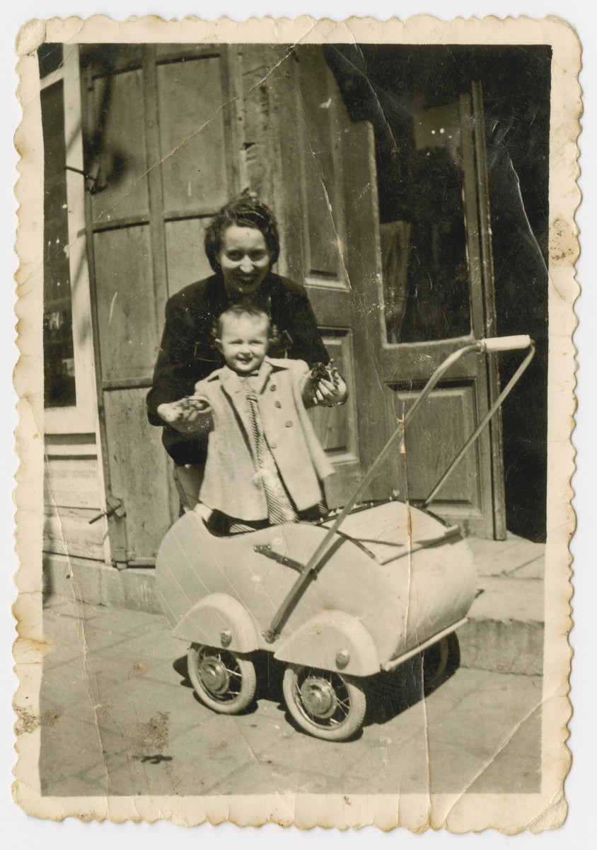 Margert Seefreund holds her daughter Suzanne standing in her baby carriage.