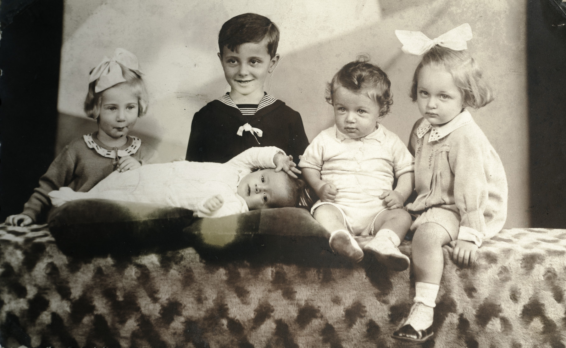 Studio portrait of five Hungarian Jewish cousins.  Judith Schonfeld is pictured on the far left.  In the center are Toni Itzkovits and his brothers (all perished).  Marika is on the far right.