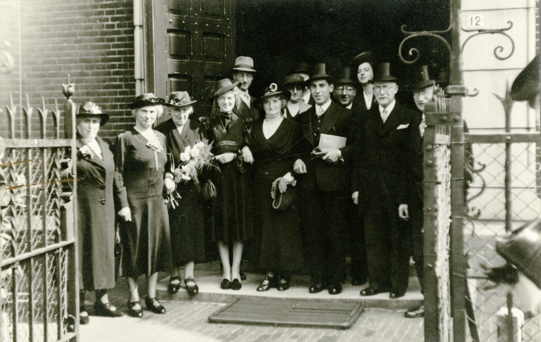 A Dutch Jewish wedding party gathers for a photo.  Pictured left to right are [unknown]; Rebecca (Reindorp) Herschel (the donor's grandmother); [unknown]; Bella (Bilha) Elizabeth Herschel (the donor's father's sister); Nico Herschel; the groom's mother; Aharon Davidson; [unknown]; [unknown]; Ammy Herschel; Herman Herschel (the donor's grandfather); and [unknown].  Pictured are Bilha (Bella) Elizabeth Herschel (the donor's father's sister, fourth from left); Nico and Ammy Herschel (the donor's parents, fifth from left and third from right); the donor's grandmother, Rebecal (Reindorp) Herschel (second from the left);  the donor's guardian and her husband, Aaron Davisdon, who perished during the war.