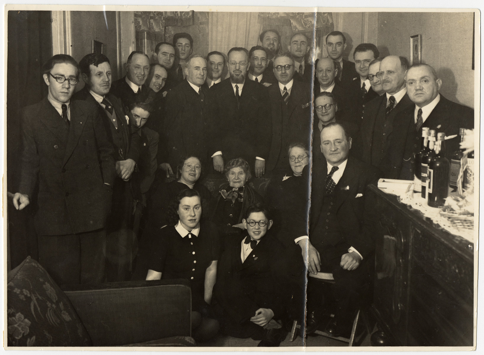 Group portrait of family and friends at a birthday celebration.  The photograph was taken on the occasion of the 75th birthday of Rosa Nachemsohn, seated in the middle.   Among those pictured is donor's father, Herman Krogman (standing to the right of the man in the middle, with glasses).