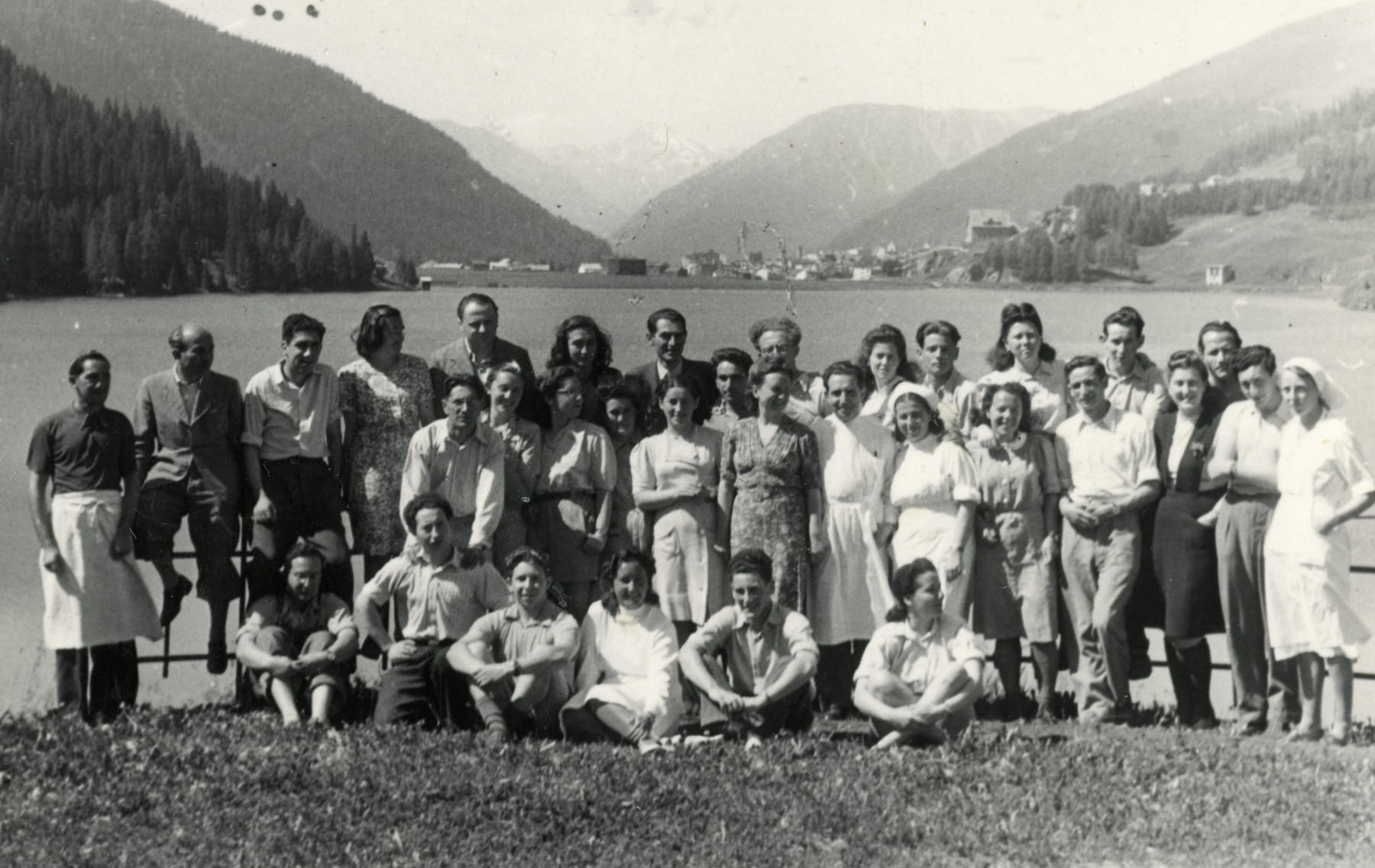 Group portrait of Jewish DPs posing next to a lake in Davos with nurses and doctors.  Yehuda Ashkenazi is pictured in the back row, sixth from the right.  Miriam Rogol is pictured in the second row, ninth from the right. Zvi Grundman is pictured in the second row, fourth from the right.