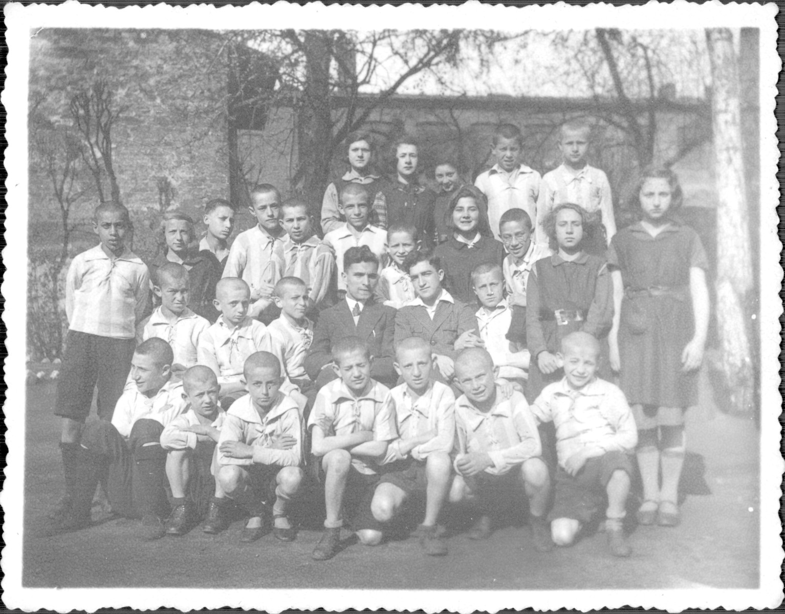Group portrait of orphans on the grounds of the Korczak Oprhanage.  Felix Gyp is in the middle right, Misha Wroblewski is on the left and Shlomo Nadel is standing on the far left.