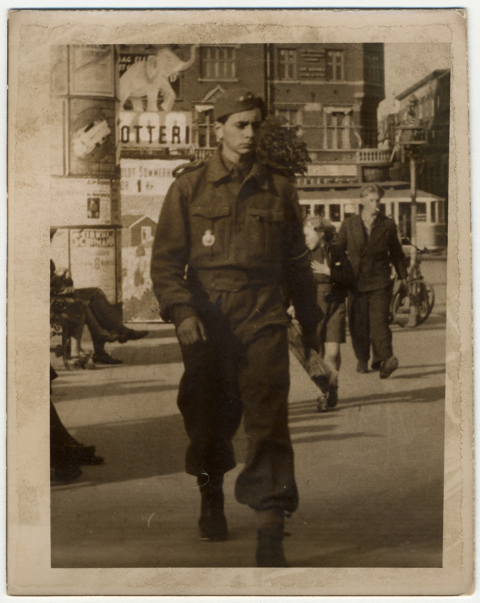 A young Jewish man in a Danish military uniform walks down a street in Denmark.   Pictured is the donor, Herbert Krogman.
