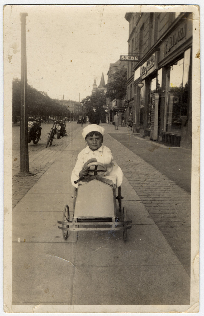 A young Jewish boy rides in a toy car on a sidewalk in Copenhagen.   Pictured is the donor, Herbert Krogman.