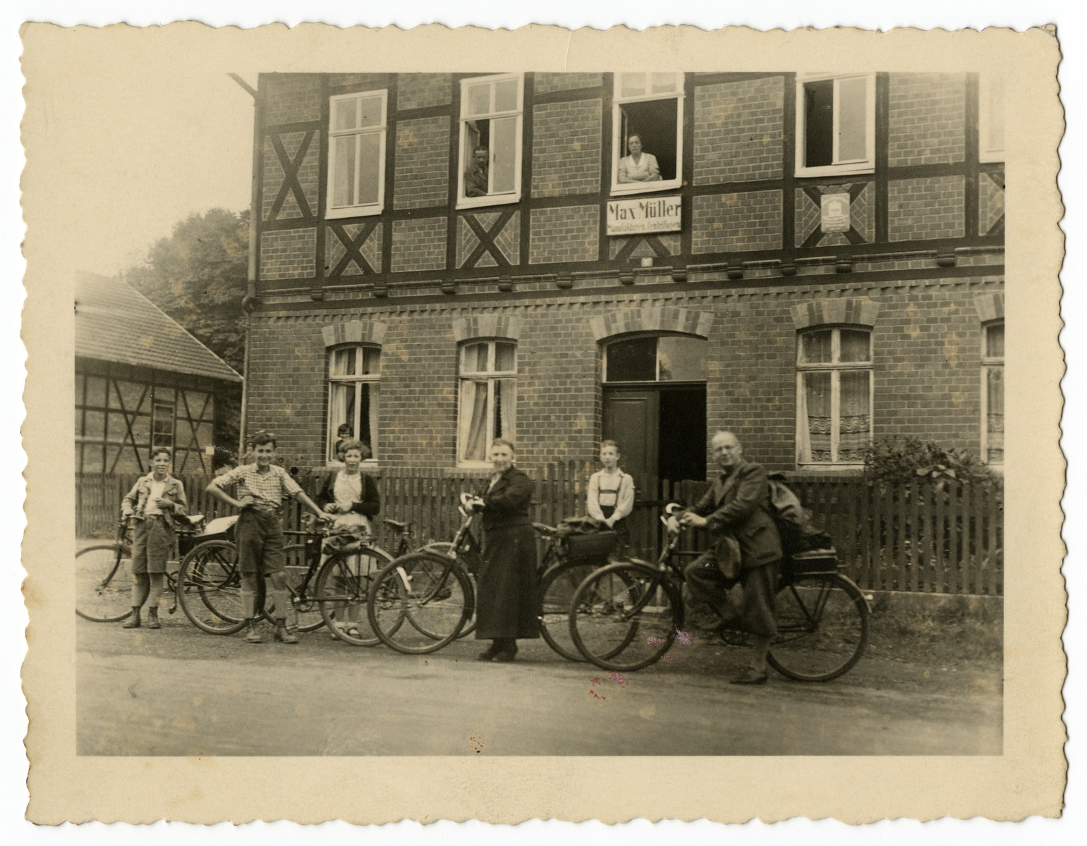 The Mueller family goes for a bicycle ride in front of the home of Sebald Mueller's brother, Max Mueller.  Standing with their bikes from left to right are:  Norbert Mueller, his cousin Ludwig Stahl, Suse Mueller, Laura Mueller and Sebald Mueller.  The young boy in the lederhosen standing in front of the gate is Norbert's cousin Willy Mueller, the son of Max Mueller, who appears in the second window from the left on the top floor. Max's wife is in the next window over.