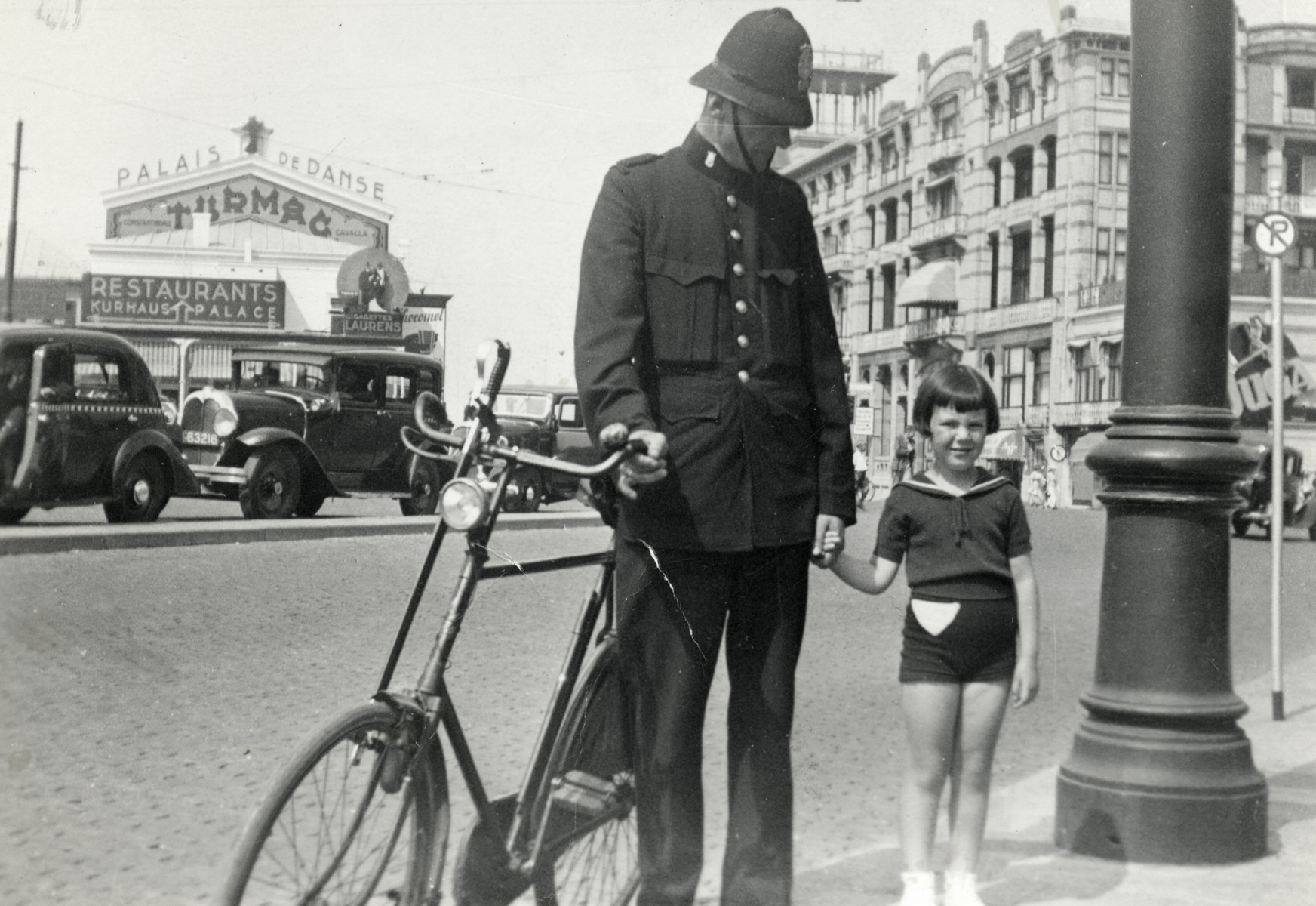 Mary Kunstenaar holds the hand of a local policeman .  The beach is behind the building.