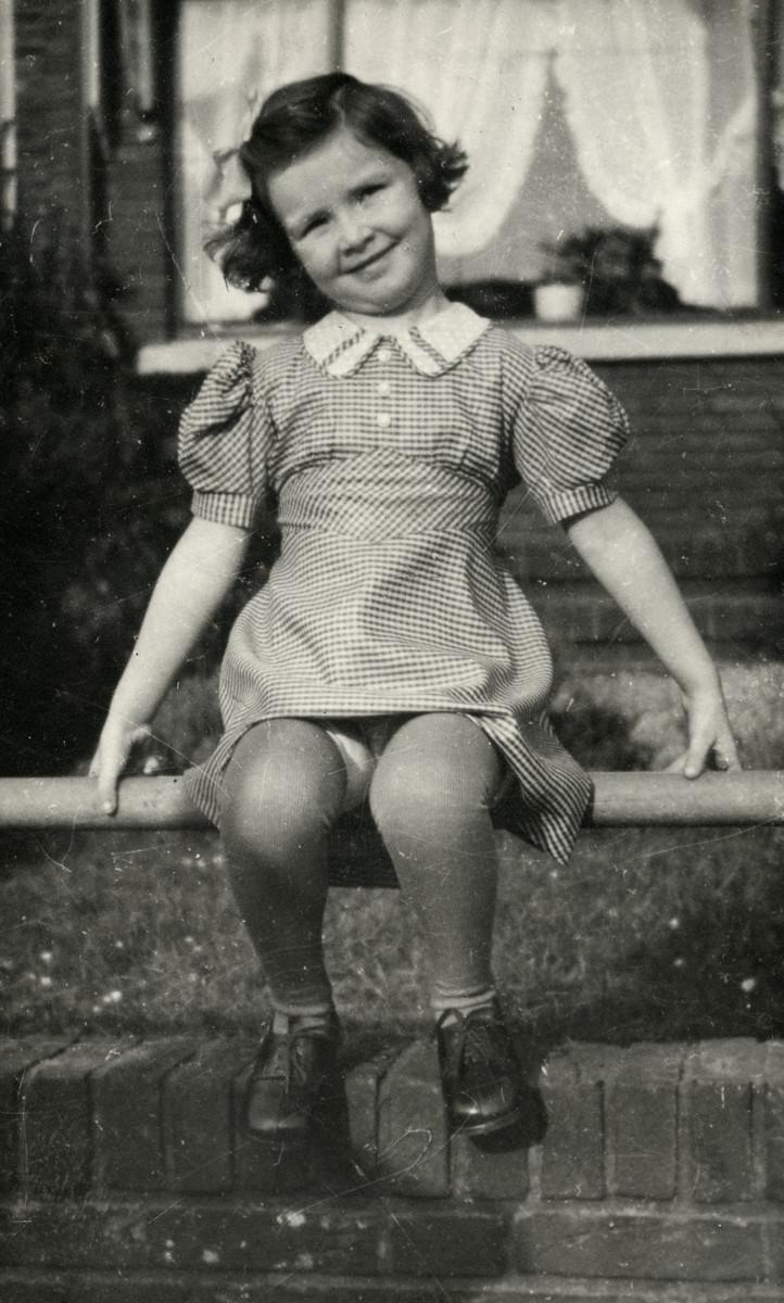 Marion Kunstenaar sits in front of  her grandparent's house.