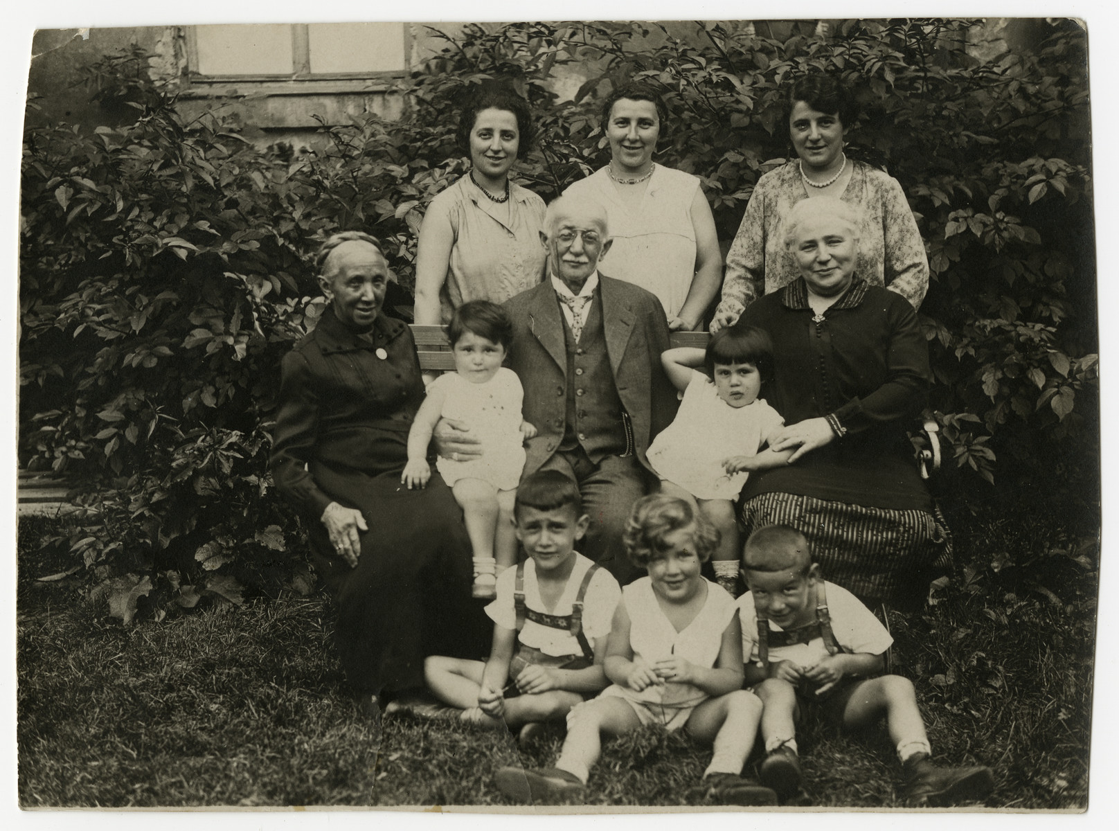 Group portrait of four generations of the Juengster family, seated outside in a garden.  Seated in front are Ludwig Stahl, Suse and Norbert Mueller.  Seated second row are Johanna Sternheimer Juengster (born May 23, 1843), Hilde Stahl, Leopold Juengster (born August 30, 1863, died June 12, 1936), Ilsa Hirsch and Clara Jacobs Juengster (born October 11, 1874, died March 26, 1942).  Standing rear are Berta Stahl, Laura Mueller and Dina Hirsch.
