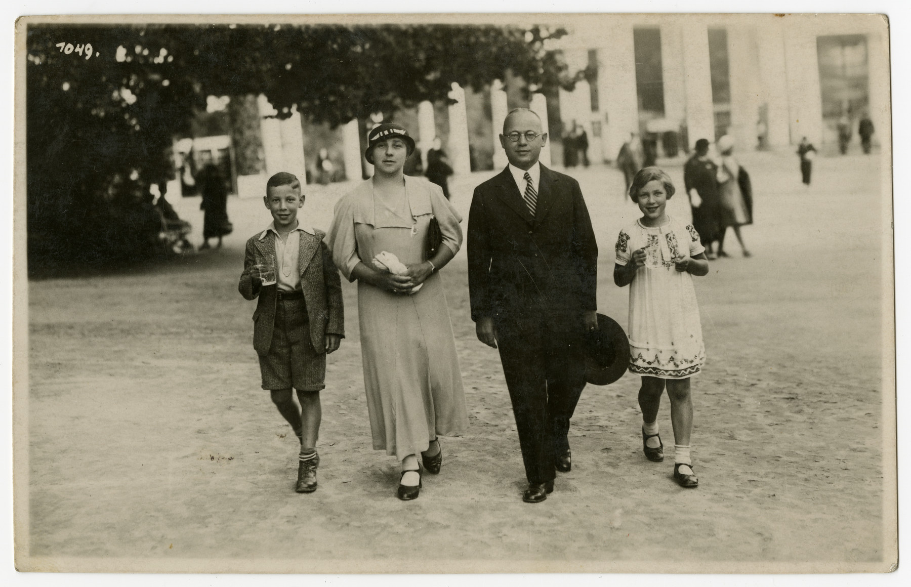 The Mueller family walks down a street of Marienbad while visiting the spa.  From left to right are Norbert, Laura, Sebald and Suse Mueller.