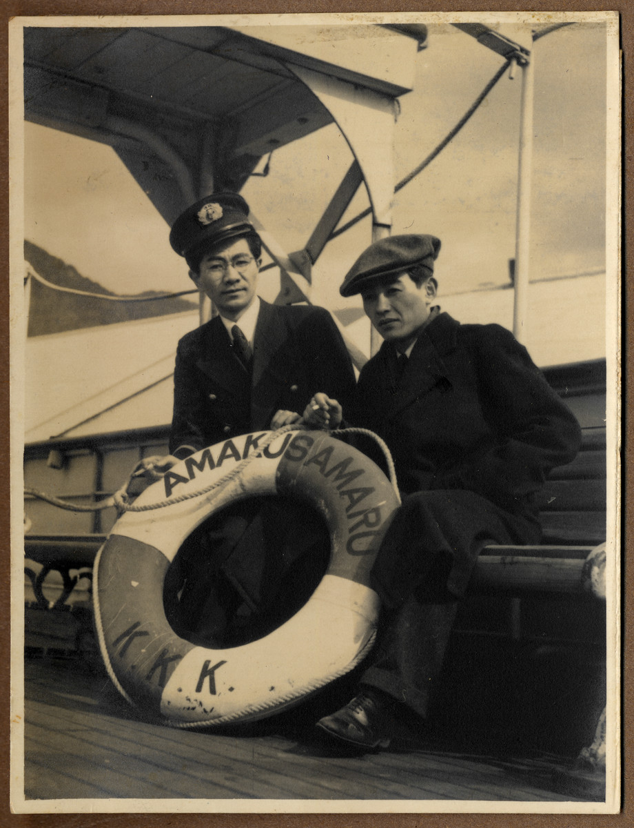 Tatsuo Osako and another crew member of the  Amakusa-maru pose on board the ship next to the life preserver.