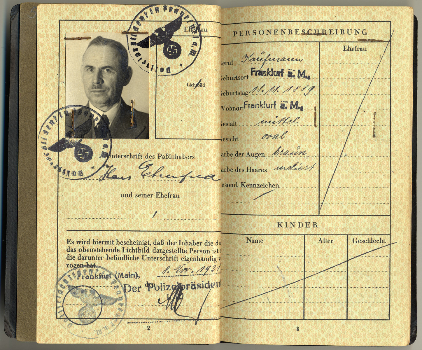 Interior page of a passport granted to Hans Ehrenfeld and stamped with Nazi seals.  The passport was dated the day before Kristallnacht.
