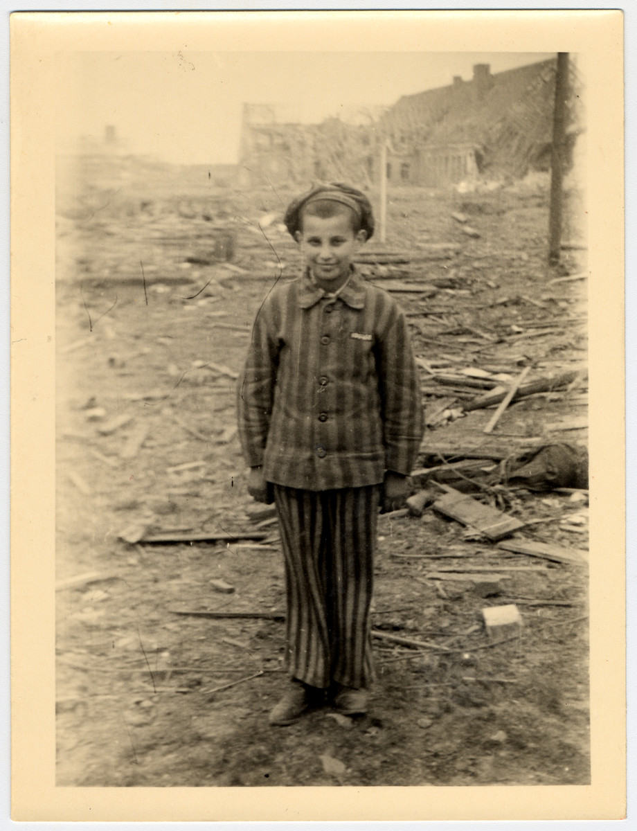 A child survivor in a uniform stands smiling amid the rubble of Nordhausen concentration camp.