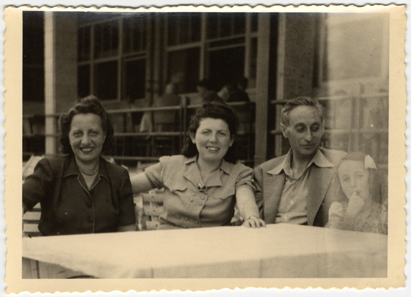 A Jewish family sits by an outdoor table after the war.  From left to right are Marta Mandler (a cousin of the donor's mother), Erszi Herzel, Ludwig Engel, and Katie Engel.