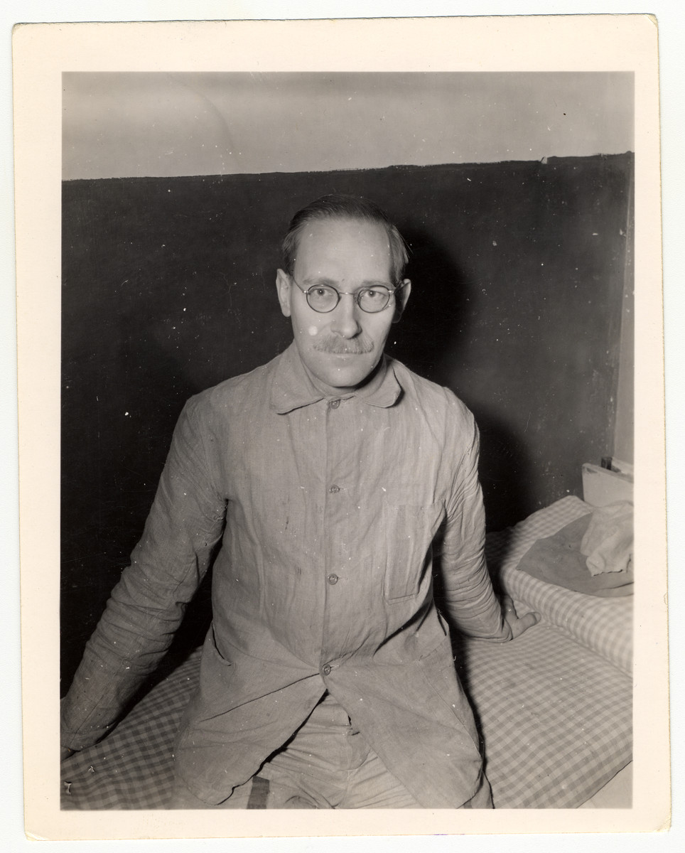 "Dr. Carl Hermann sits on bed in Halle Jail.  Caption reads: ""Dr. Carl Hermann, a Quaker, has been a prisoner of the Nazis since May 5, 1943. He is a German, but anti-Nazi. He and his wife gave shelter to a Jewish family and listened to foreign broadcasts. Dr. Hermann is a physicist by profession and worked in a synthetic oil plant near Berlin before he was taken prisoner by the Gestapo and placed in Halle Jail."