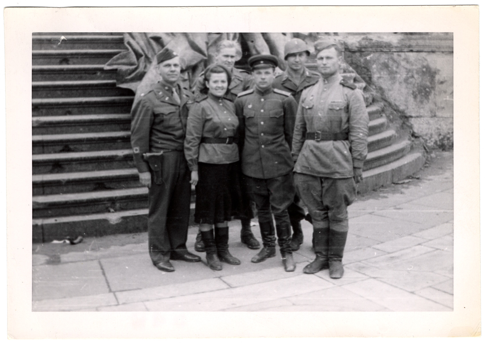 Lt. Col. Ralph E. Willey and Lt. Plevinsky pose with Russian soldiers on the steps of the Russian headquarters in Berlin.