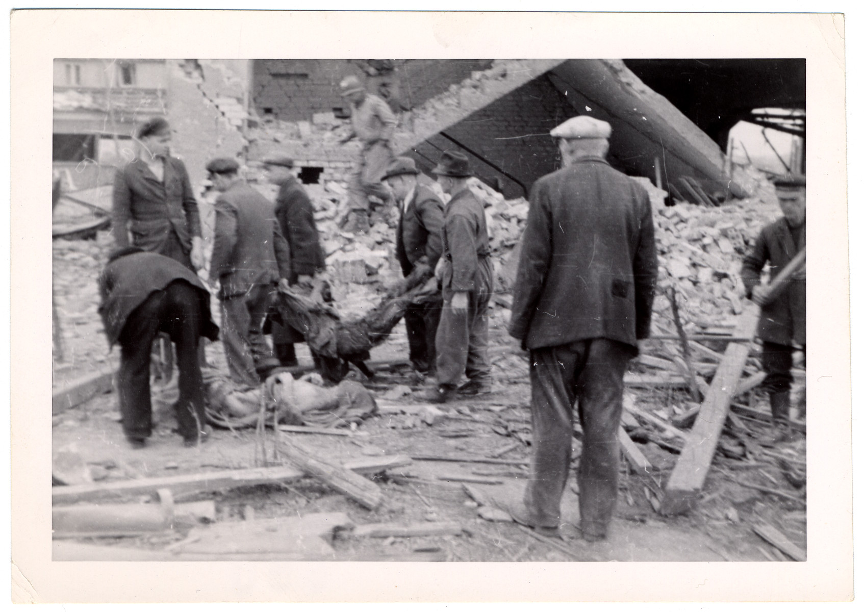 German civilians remove a corpse from the rubble of the Nordhausen concentration camp while other civilians watch and an American soldier walks in the background.