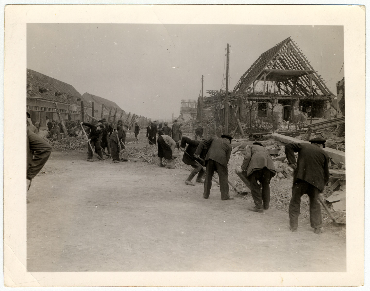 """German civilians clear rubble from the Nordhausen camp to make room for corpses that were to be piled there.  Photo caption reads: """"German civilians clear rubble from N yard of Lager Nordhausen, a Gestapo concentration camp near Nordhausen, Germany, in order to make room for bodies of several hundred inmates who died of starvation or were shot by Gestapo men. The concentration camp, according to G-2, 104th Infantry Division, 1st U.S. Army, had from 3,000 to 4,000 inmates, including French, Polish, Belgian, a few Russian and several German political prisoners. All the prisoners were maltreated, beaten and starved."""""""