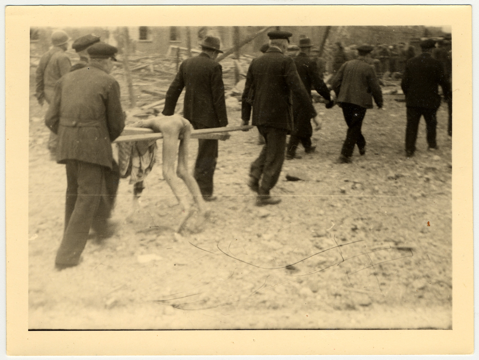German civilians carry a corpse, using pieces of wood as a stretcher, from the Nordhausen concentration camp for burial.