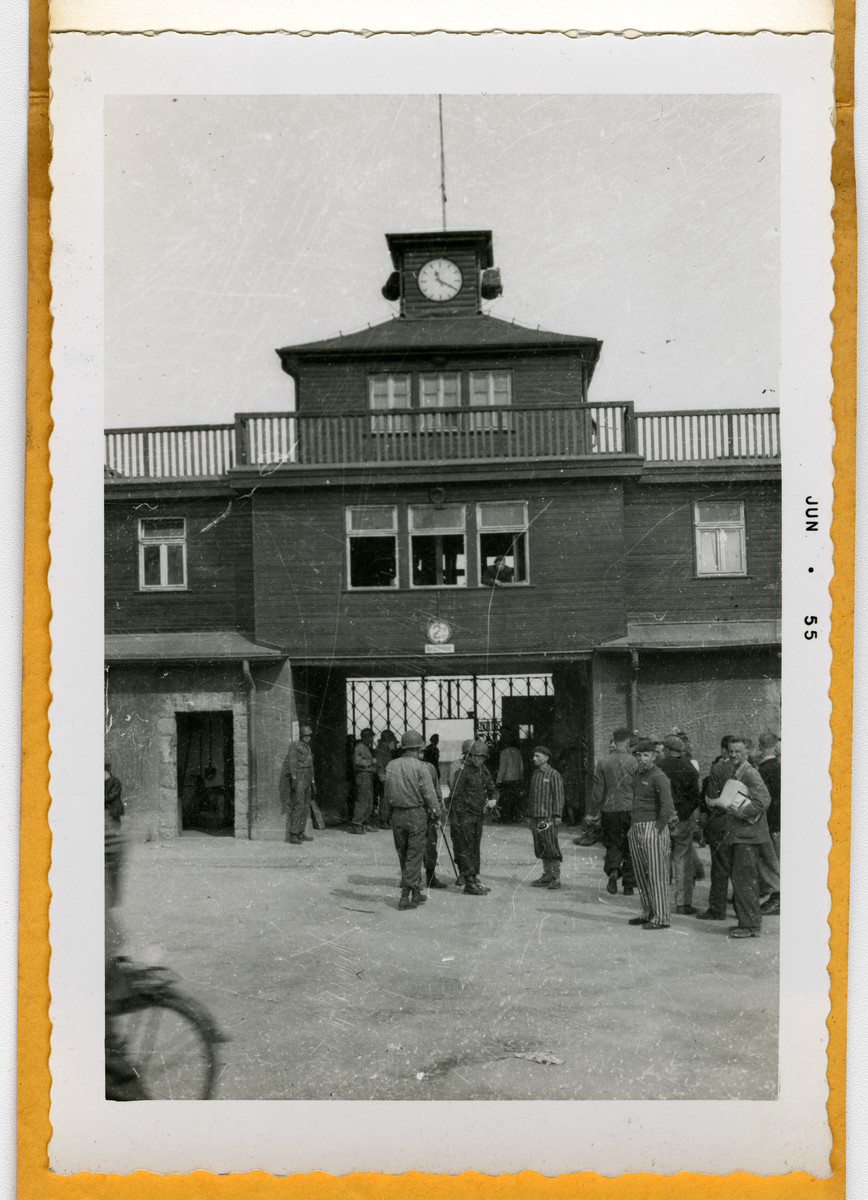American soldiers and survivors mingle by the entrance to the Buchenwald concentration camp following liberation.