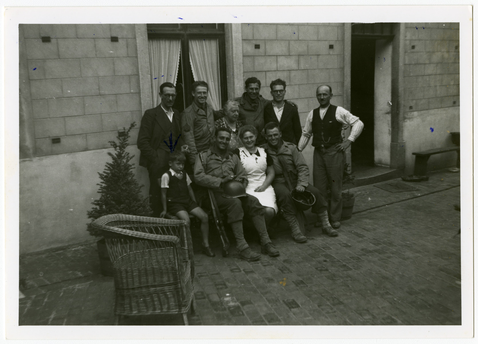 American soldiers liberate the town of Perwez.  Pictured in the center is Mrs. Hemptine Stas, the wife fo the butcher, who was hiding the Jewish child Albert Szabo (seated left).  She lived next door to the Henrards, the rescuers of Simon Steil.