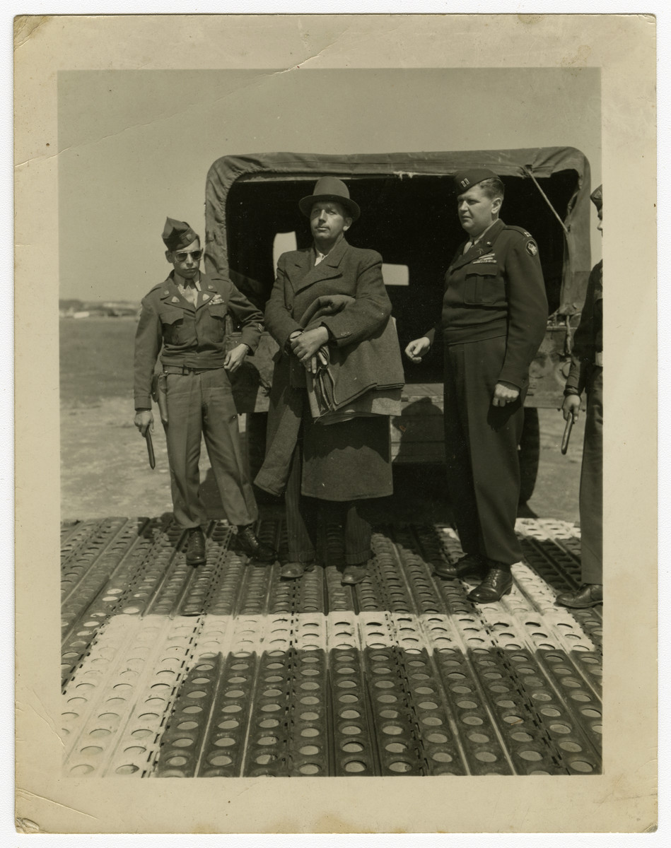 "Josef Buehler is brought in handcuffs to the airport to be flown to Poland for trial as a war criminal.  Original caption reads, ""Josef Buehler, deputy to Hans Frank, arrives by truck under guard by Captain Binder and Private Charles F. Sylvia to be turned over to the Polish Government for trial as war criminals. Buehler with two other Ex-Nazi officials, were held at Nurnberg, Germany as witnesses at the International Military Tribunal trials. Seven other defendants were flown from Frankfurt by the AAF Airport to Furth, Nurnberg, and were met by three from Nurnberg, making a total of ten men being turned over by the Americans to the Polish Government to be tried as war criminals."" [sic]  The photo is dated 25 May and is credited to photographer PFC Eddie Murphy of the U.S. Army Signal Corps."
