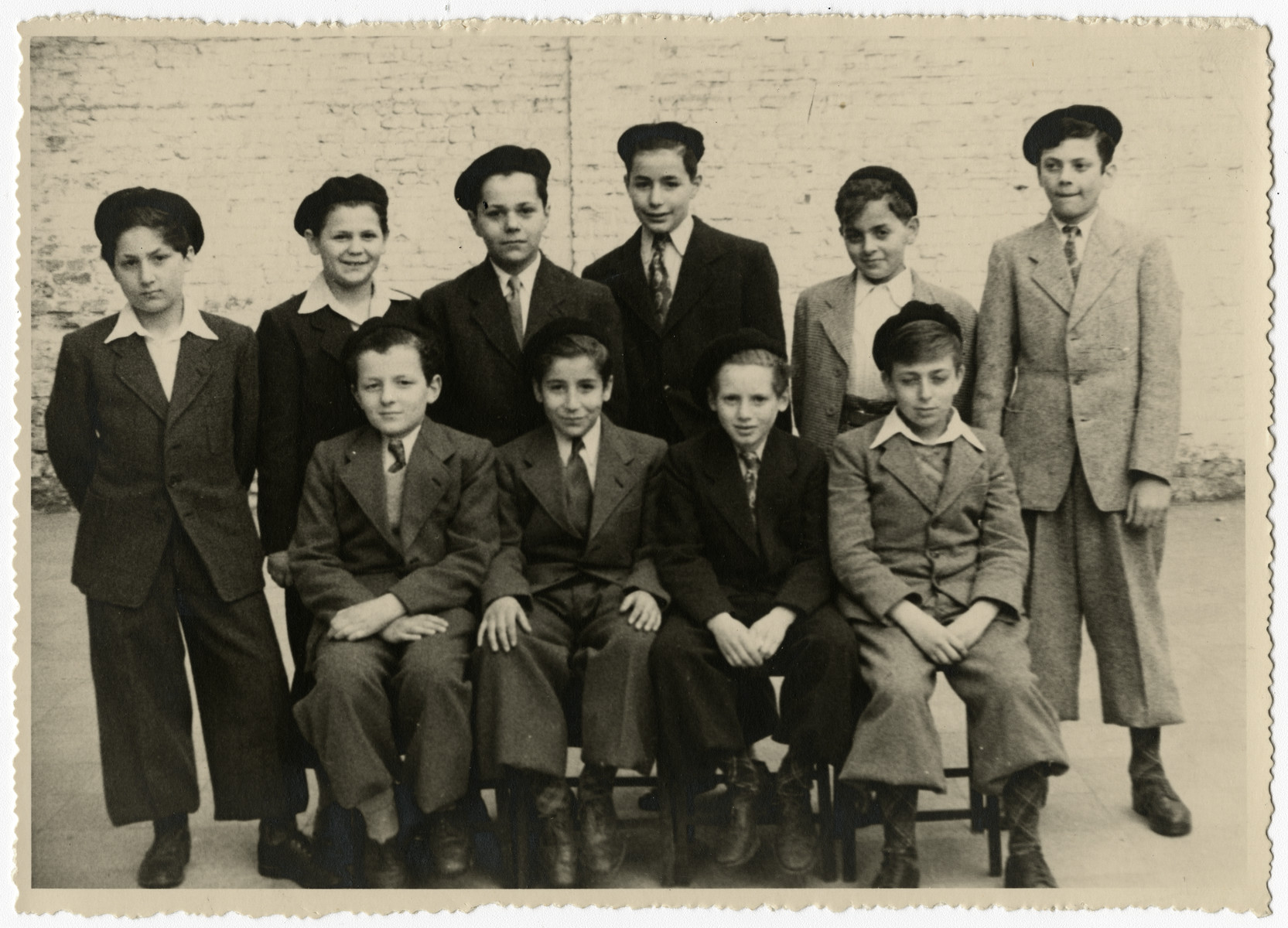 Group portrait of orphans in the postwarTiefenbrunner children's home in Antwerp.  Pictured sitting are Boris Bornstein (center) and Jacques Fedder (right).  Standing left to right are: Simon Steil, Kalman, Sami, Leopold Moll, Charles Bornstein and unidentified.