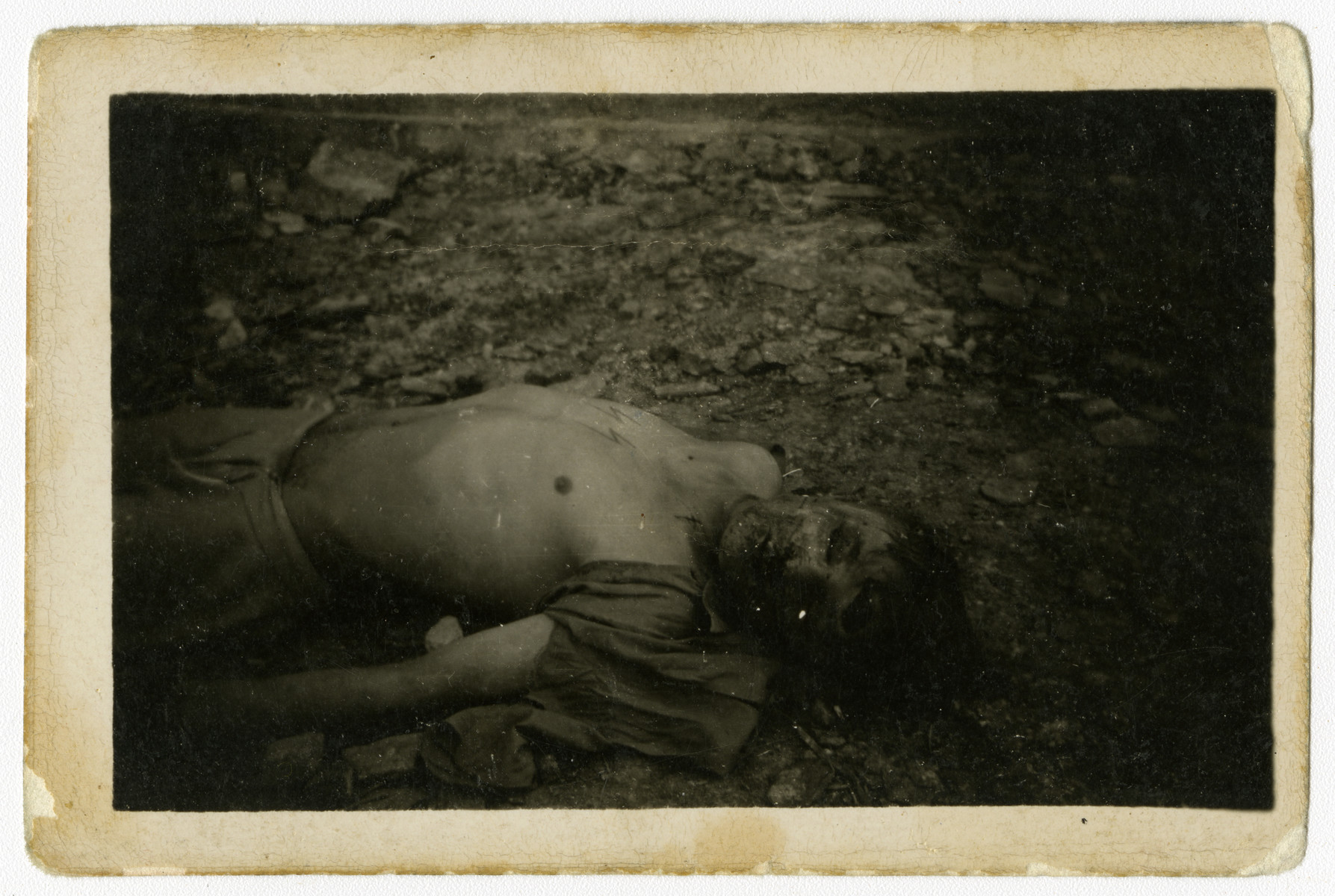 Close-up of the corpse of a former SS guard; his shirt has been torn off exposing his SS tattoo.